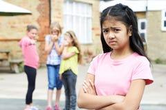 Fille malheureuse bavardé environ par des amis d'école Photographie stock libre de droits