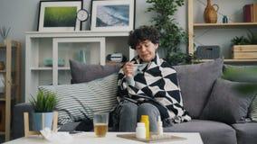 Fille malheureuse prenant la température corporelle avec le thermomètre se reposant sur le sofa à la maison clips vidéos