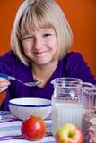 Fille mangeant des cornflakes Image stock