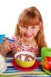 Fille mangeant des cornflakes de chocolat Photos stock