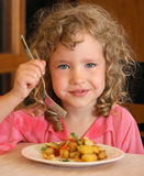 Fille mangeant des pommes de terre Image libre de droits