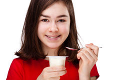 Fille mangeant du yaourt Photo stock