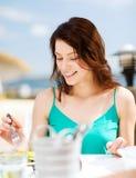 Fille mangeant en café sur la plage Photographie stock libre de droits