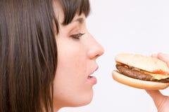 Fille mangeant l'hamburger Images stock