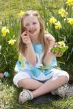 Fille mangeant l'oeuf de chocolat sur la chasse à oeuf de pâques Images libres de droits