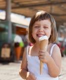 Fille mangeant la crème glacée à la rue Images stock