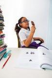 Fille mangeant la crême glacée de chocolat dans la chambre de classe Image libre de droits