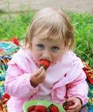 Fille mangeant la fraise Photographie stock libre de droits