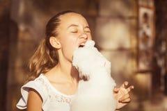 Fille mangeant la sucrerie de coton douce Photographie stock
