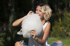 Fille mangeant la sucrerie de coton douce en parc d'été Images stock