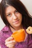Fille mangeant le biscuit et buvant du café Photographie stock libre de droits