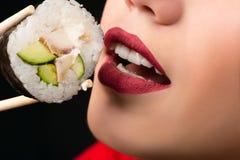 Fille mangeant le plan rapproché de petit pain de sushi image stock