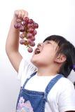 Fille mangeant le raisin Photo stock