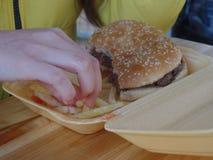 Fille mangeant un hamburger et des pommes chips photo stock