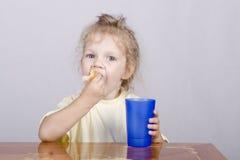 Fille mangeant un petit pain avec du jus à la table Image stock