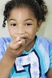Fille mangeant un pice de gâteau/de nourriture image stock