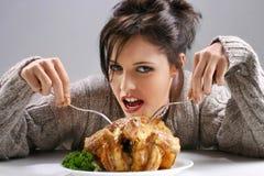 Fille mangeant un poulet Photos stock