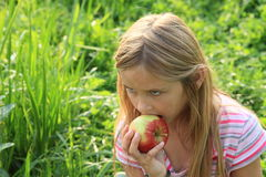 Fille mangeant une pomme Photographie stock