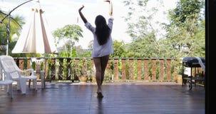 Fille marchant à la vue arrière de dos de terrasse, bras de bout droit regardant le jardin tropical clips vidéos