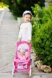 Fille marchant avec la poussette Photographie stock libre de droits