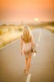 Fille marchant avec sa planche à roulettes Image libre de droits