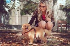 Fille marchant avec un chien dans la ville Pomerani espiègle et animé Images libres de droits