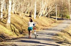 Fille marchant avec un vélo en parc Image stock