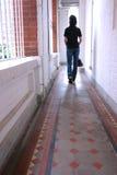 Fille marchant dans un long couloir Photographie stock libre de droits