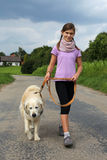 Fille marchant son chien Photographie stock