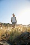 Fille marchant sur la colline en soleil Image stock