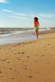 Fille marchant sur la plage Photographie stock libre de droits