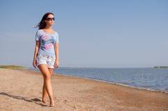 Fille marchant sur la plage Images stock
