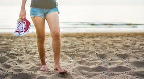 Fille marchant sur la plage tenant des espadrilles Images stock