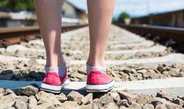 Fille marchant sur la voie de voie ferrée dans les haut-parleurs rouges Images stock