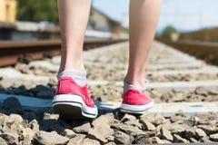 Fille marchant sur la voie de voie ferrée dans les haut-parleurs rouges Image stock