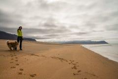 Fille marchant sur le littoral scénique de l'Islande avec le chien Photos stock