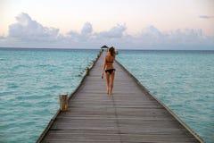 Fille marchant sur le pilier, îles des Maldives Image libre de droits