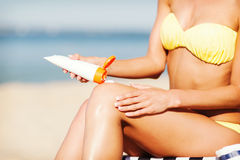 Fille mettant la crème de protection du soleil sur la chaise de plage Photographie stock libre de droits