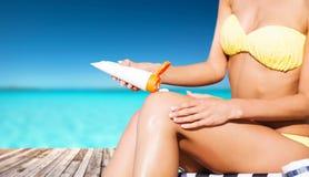 Fille mettant la crème de protection du soleil sur la couchette Photo stock