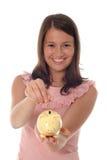 Fille mettant la pièce de monnaie à la tirelire Photos libres de droits