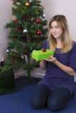 Fille mettant le cadeau de Noël sous l'arbre images libres de droits