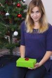 Fille mettant le cadeau de Noël sous l'arbre photo libre de droits