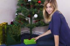 Fille mettant le cadeau de Noël sous l'arbre photos stock