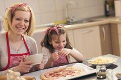 Fille mettant le salami sur la pâte de pizza images libres de droits