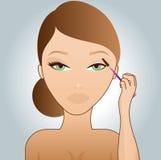 Fille mettant sur le mascara Photo stock