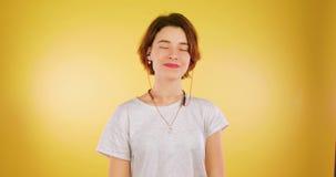 Fille mignonne écoutant la musique dans des écouteurs sans fil, dansant et souriant au-dessus du fond jaune Technologie, musique banque de vidéos