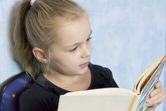 Fille mignonne affichant un livre Photos stock