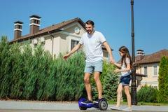 Fille mignonne aidant son hoverboard de tour de père Photo stock