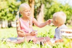 Fille mignonne alimentant un petit enfant en parc photographie stock libre de droits