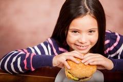 Fille mignonne appréciant un hamburger image stock